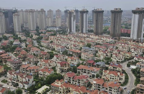 A block of villa residences is seen in front of new residential buildings under construction in Shenyang, Liaoning province July 18, 2013. R