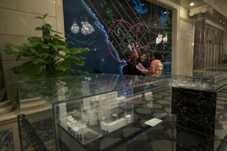 A property sales agent (L) shows a potential buyer an electronic map of the Qianhai special economic zone in Shenzhen August 16, 2013. REUTE