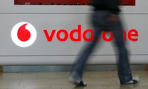 A customer walks past the Vodafone logo in a shopping mall in Prague February 7, 2012. British telecommunication firm Vodafone is expected t