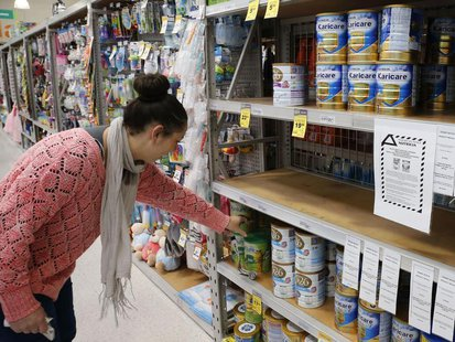 A woman browses for milk powder at a stand with a food recall notice from Nutricia in a supermarket in Huntly, Waikato Region in New Zealand