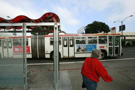 A passenger walks to catch a bus at a solar powered bus stop in San Francisco, California November 4, 2009. REUTERS/Robert Galbraith