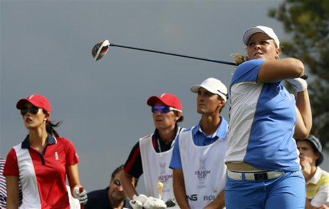 Caroline Hedwall of Team Europe tees off of the 15th as opponent Michelle Wie of Team USA (L) watches in the singles matches of their 2013 S