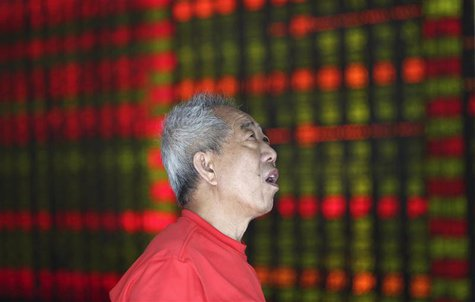 An investor looks at an electronic board showing stock information at a brokerage house in Shenyang, Liaoning province August 16, 2013. REUT