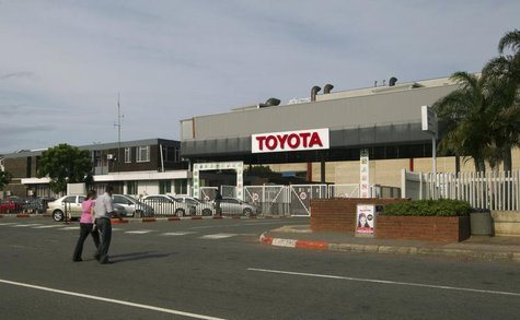 People walk near Toyota Motor Corp's Durban car factory, which has been forced to shut down for four days due to an illegal pay strike by em