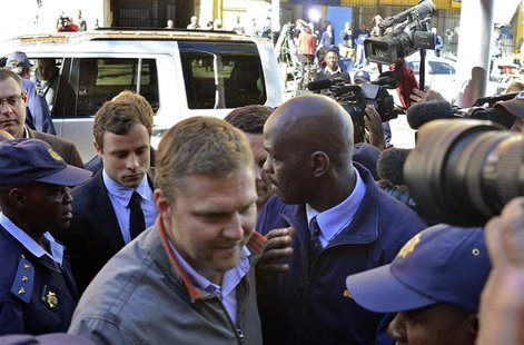 Paralympic gold medallist Oscar Pistorius (foreground, 3rd L) arrives at the Pretoria Magistrates court August 19, 2013. REUTERS/Mujahid Saf