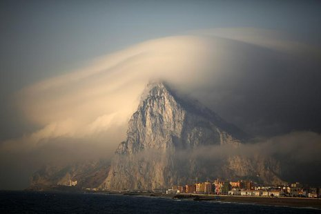 A cloud partially covers the tip of the Rock of the British territory of Gibraltar at sunrise from La Atunara port before Spanish fishermen