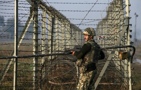 An Indian Border Security Force (BSF) soldier patrols near the fenced border with Pakistan in Suchetgarh, southwest of Jammu January 11, 201