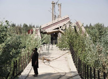 A fighter from the Islamist Syrian rebel group Jabhat al-Nusra stands on the historical Deir al-Zor Suspension Bridge, damaged by what activ