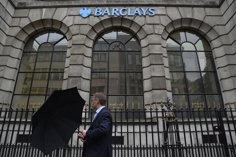 A man lifts his umbrella as he walks past a branch of Barclays bank in London July 30, 2013. . REUTERS/Toby Melville