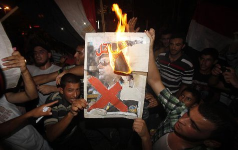 Palestinians burn a poster of Egypt's army chief General Abdel Fattah al-Sisi during a rally in support of Egypt's deposed Islamist Presiden