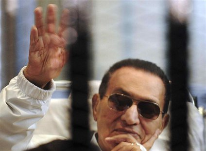 Former Egyptian President Hosni Mubarak waves to his supporters inside a cage in a courtroom at the police academy in Cairo, in this file pi