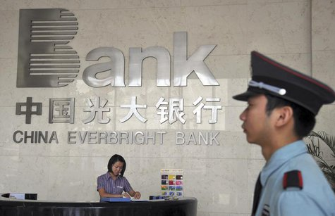 A security personnel on duty stands next to the reception desk at a branch of China Everbright Bank in Hefei, Anhui province August 18, 2010