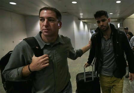 U.S. journalist Glenn Greenwald (L) walks with his partner David Miranda in Rio de Janeiro's International Airport August 19, 2013. REUTERS/