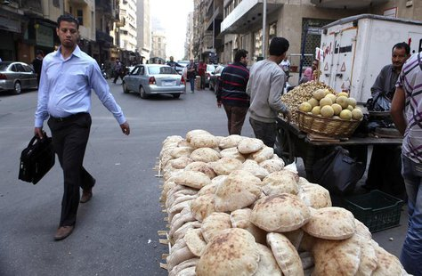 A man walks past a bread stand at a street corner in central Cairo April 11, 2013. REUTERS/Asmaa Waguih