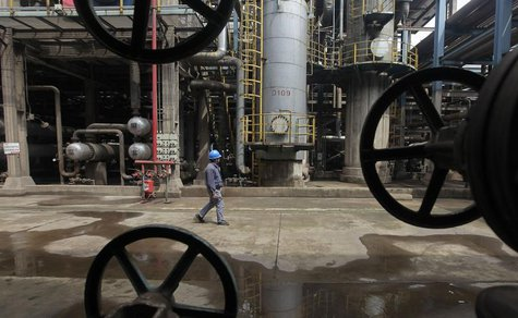 A worker walks past oil pipes at a refinery in Wuhan, Hubei province March 23, 2012. REUTERS/Stringer