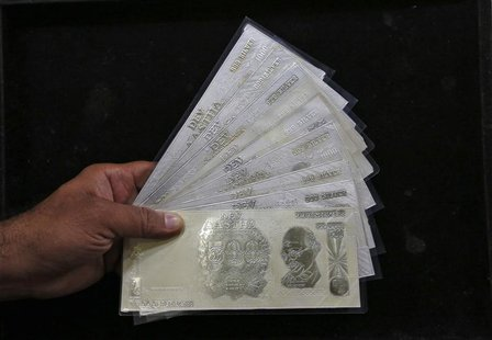 A jeweller poses with silver plates in the form of Indian rupee notes inside a showroom in New Delhi August 19, 2013. REUTERS/Mansi Thapliya