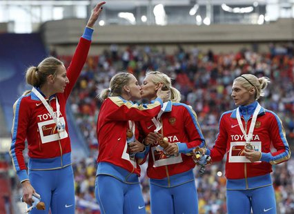 Gold medallists team Russia kiss and celebrate at the women's 4x400 metres relay victory ceremony during the IAAF World Athletics Championsh