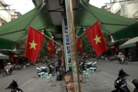 A Vietnamese boy is reflected in a mirror along a street decorated with national flags, in downtown Hanoi October 27, 2010. REUTERS/Damir Sa