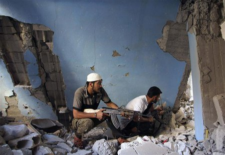 Free Syrian Army fighters take cover inside a damaged house in Deir al-Zor August 19, 2013. REUTERS/Khalil Ashawi