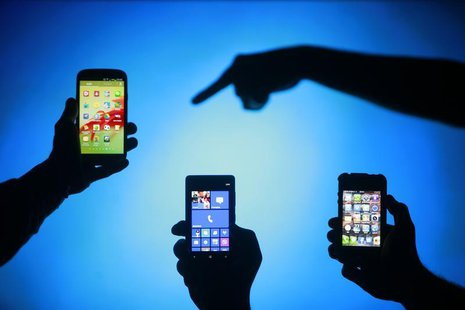 Men are silhouetted against a video screen as they pose with Samsung Galaxy S3, Nokia Lumia 820 and iPhone 4 smartphones (L-R) in this photo