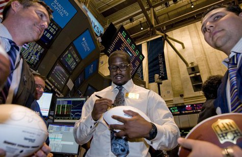 NFL draft prospect Von Miller signs a football for traders on the New York Stock Exchange floor before he rings the closing bell in New York