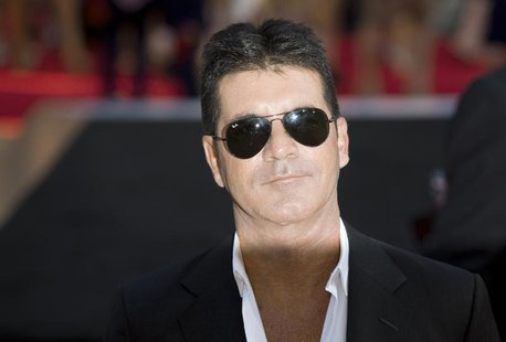 "Television mogul Simon Cowell poses for photographers as he arrives for the film ""One Direction: This is Us"", in London August 20, 2013. REU"