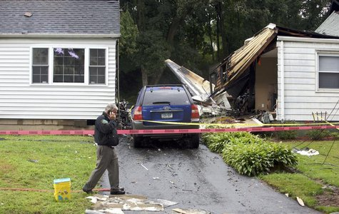 The remains of a plane is seen next to a damaged home after it crashed in East Haven, August 9, 2013. REUTERS/Michelle McLoughlin