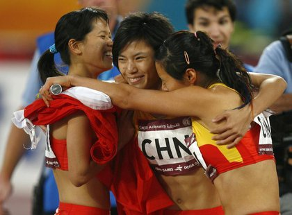 China's (L-R) Han Ling, Wang Jing and Qin Wangping celebrate after winning the women's 4x100m relay race final during the 15th Asian Games i