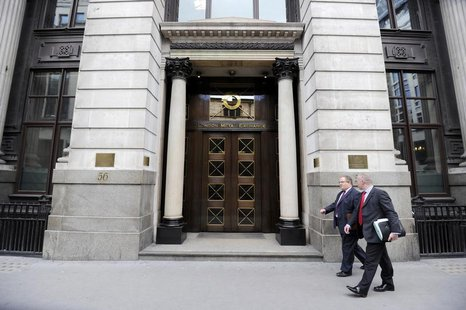 Men walk past the London Metal Exchange (LME) in London, July 22, 2011. REUTERS/Paul Hackett