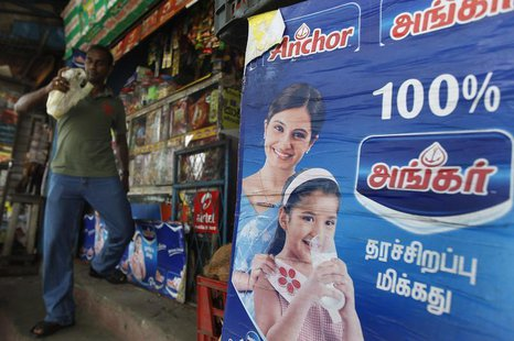 An advertisement for Fonterra's Anchor powder brand is seen at a shop as a customer walks by in Colombo August 15, 2013, a day before the an
