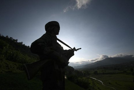 An Indian army soldier stands guard while patrolling near the Line of Control, a ceasefire line dividing Kashmir between India and Pakistan,