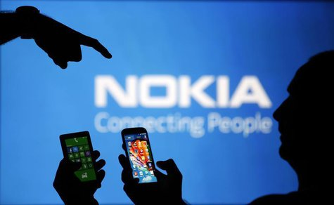 Men are silhouetted against a video screen with an Nokia logo as he poses with an Nokia Lumia 820 and Samsung S4 smartphones in this photo i