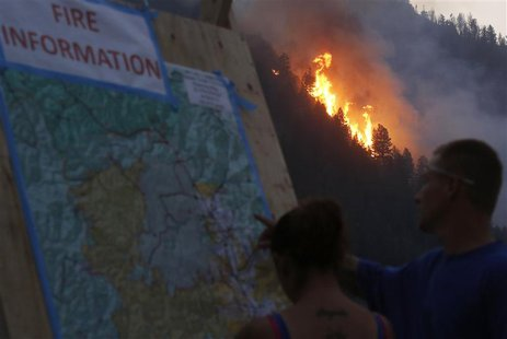 People look at a map of the fire as flames leap at the Beaver Creek wildfire outside Hailey, Idaho August 18, 2013. REUTERS/Jim Urquhart