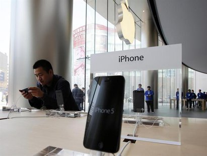 A visitor tries out an iPhone at an Apple store in Beijing April 2, 2013. REUTERS/Kim Kyung-Hoon
