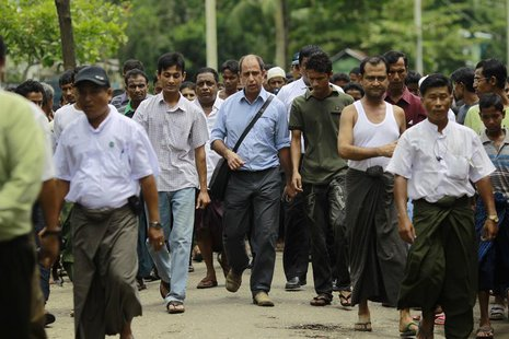 Tomas Ojea Quintana (C), United Nations Special Rapporteur on the human rights situation, walks with Rohingya Muslims as he visits Aung Ming