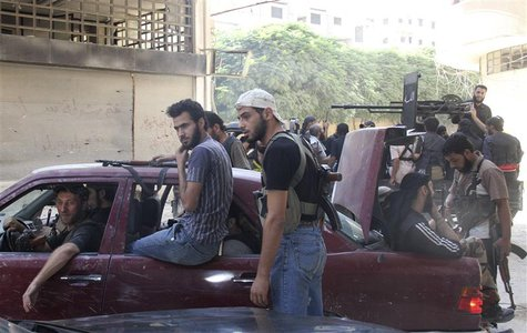Free Syrian Army fighters carry their weapons and sit in cars and pick-up trucks near the frontline in the refugee camp of Yarmouk, near Dam