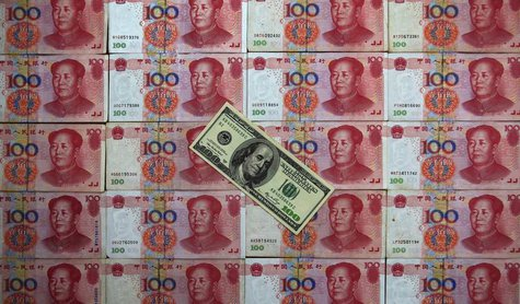 A U.S. $100 banknote is placed on top of 100 yuan banknotes in this picture illustration taken in Beijing May 7, 2013. REUTERS/Petar Kujundz
