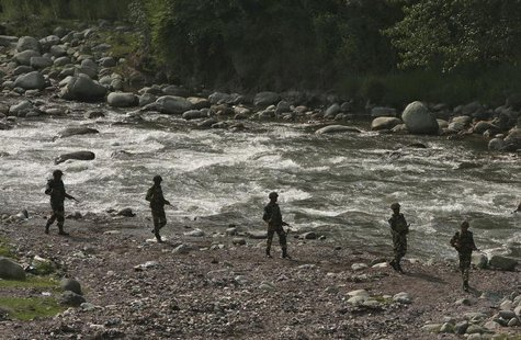 Indian Border Security Force (BSF) soldiers patrol next to a stream near the Line of Control (LoC), a ceasefire line dividing Kashmir betwee