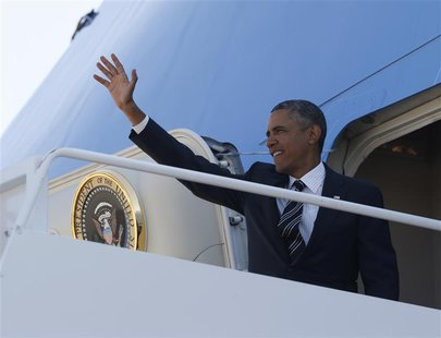 U.S. President Barack Obama waves from Air Force One at Andrews Air Force Base near Washington, August 22, 2013. REUTERS/Jason Reed