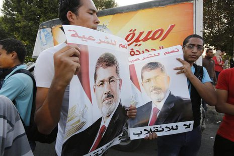 Supporters of deposed Egyptian President Mohamed Mursi hold up posters of him during a protest along Zahara street in Cairo August 18, 2013.