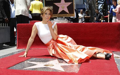 Singer and actress Jennifer Lopez blows a kiss at photographers as she poses on her star after it was unveiled on the Walk of Fame in Hollyw