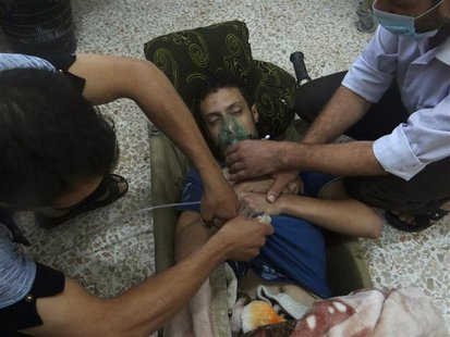 A man, affected by what activists say is nerve gas, breathes through an oxygen mask in the Damascus suburbs of Jesreen August 21, 2013. REUT