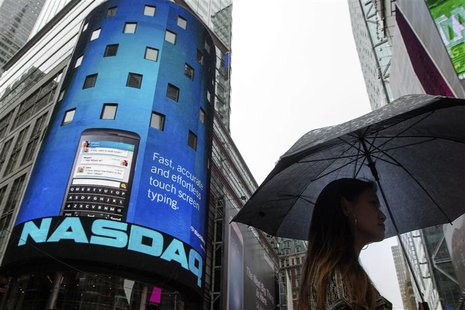 A woman holds an umbrella as she walks past the Nasdaq MarketSite in New York's Times Square, August 22, 2013. REUTERS/Lucas Jackson