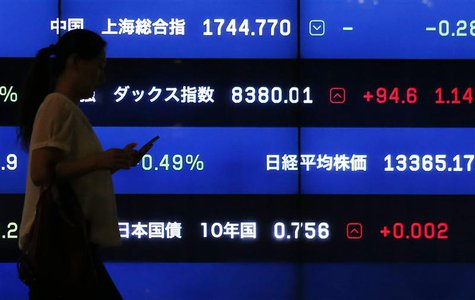 A woman walks past a screen showing market indices in Tokyo August 22, 2013. REUTERS/Issei Kato