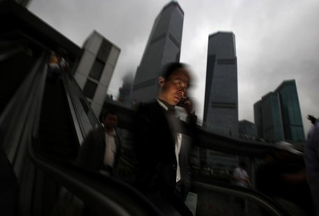 A businessman talks on his mobile phone as he walks in the financial area of Pudong in Shanghai May 30, 2013. REUTERS/Carlos Barria