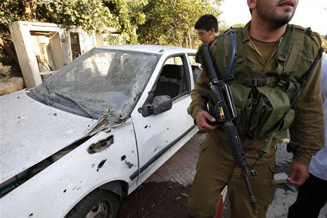 An Israeli soldier walks past a car damaged by a barrage of Lebanese rockets fired at Israel, in Kibbutz Gesher HaZiv, near the northern cit