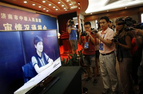 Journalists take pictures and videos of a screen displaying a court's microblog page showing a video of Gu Kailai, wife of ousted Chinese Co
