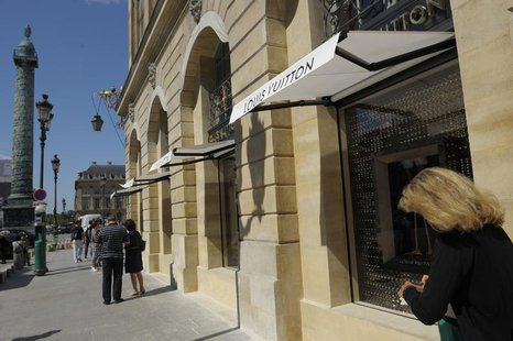 A woman walks past the LVMH's Louis Vuitton's jewellery store on Place Vendome during its opening day in Paris July 2, 2012. REUTERS/Philipp