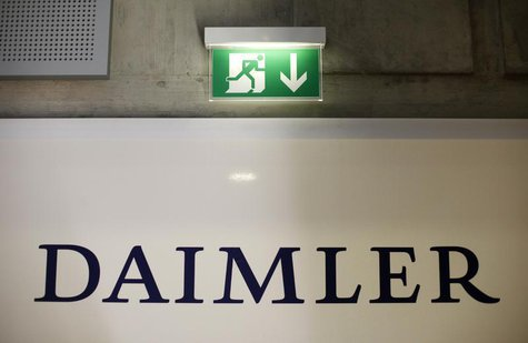 A emergency exit sign is pictured above a logo of German car manufacturer Daimler AG, before the annual news conference in Stuttgart in this