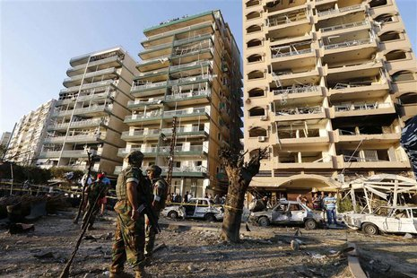 Lebanese army soldiers stand near damaged buildings caused by the two explosions outside two mosques in Lebanon's northern city of Tripoli,